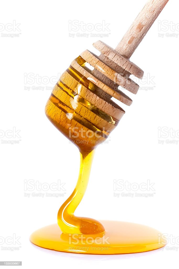 Honey dripping from dipper stock photo