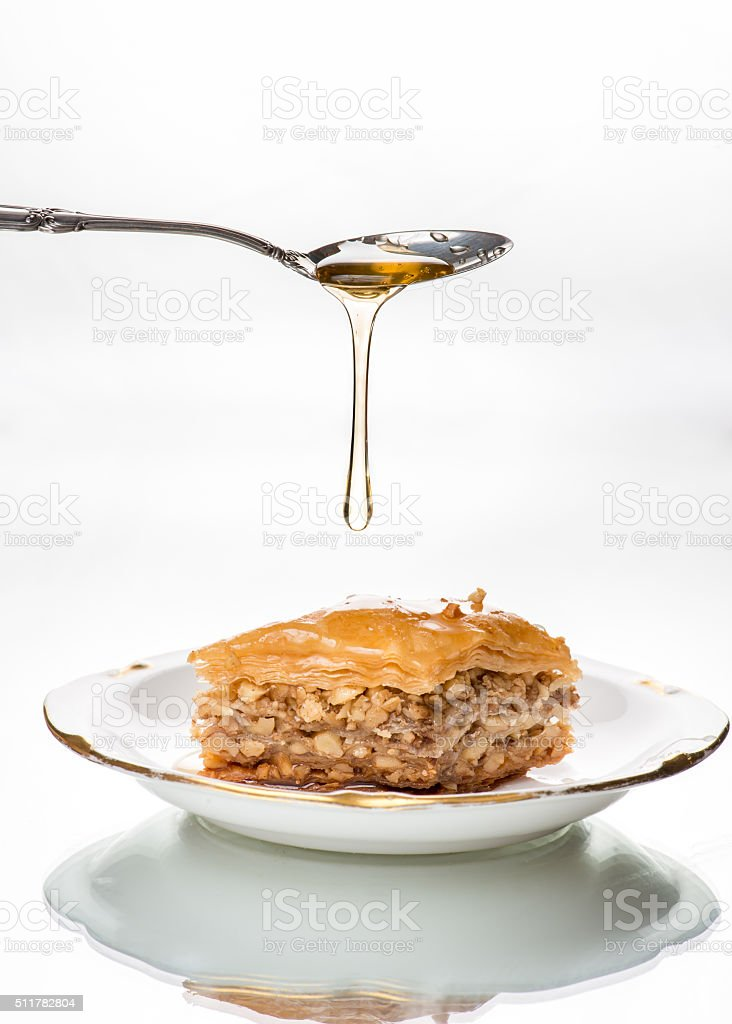 Honey dripping from sterling silver spoon onto baklava stock photo