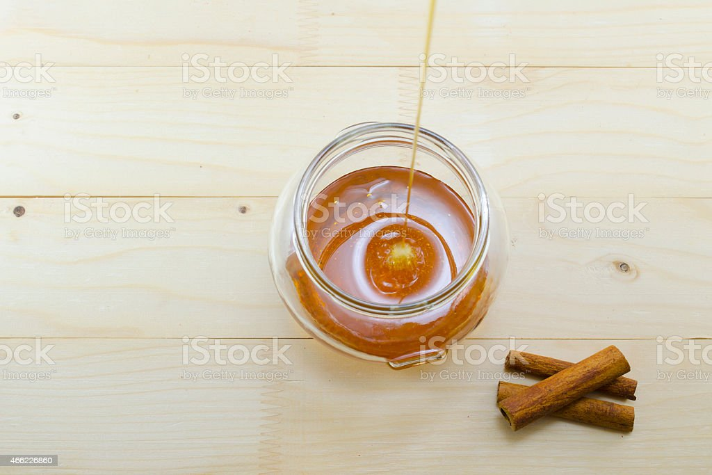Honey dripping into a glass jar royalty-free stock photo