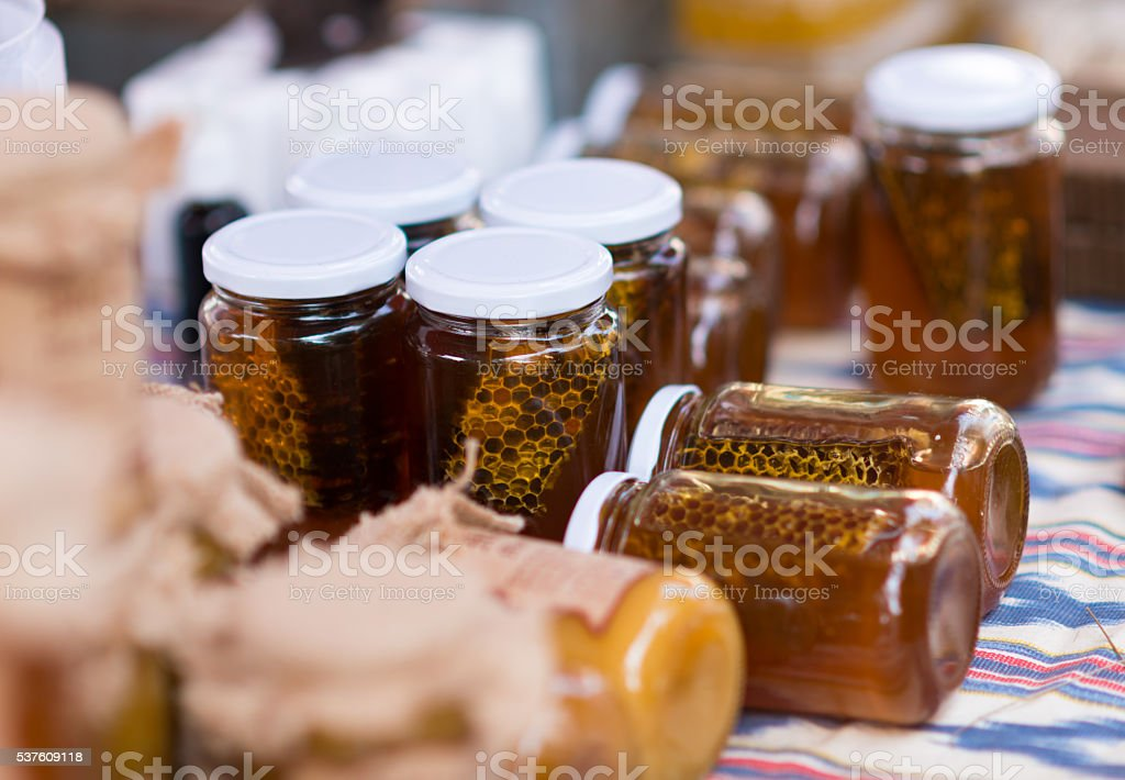 honey glasses with honeycomb at a market stall stock photo