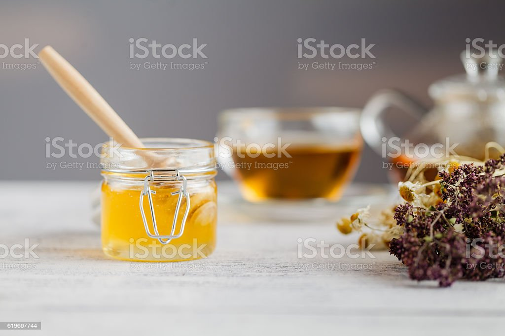Honey in a glass jar and herbal tea. Honey and stock photo
