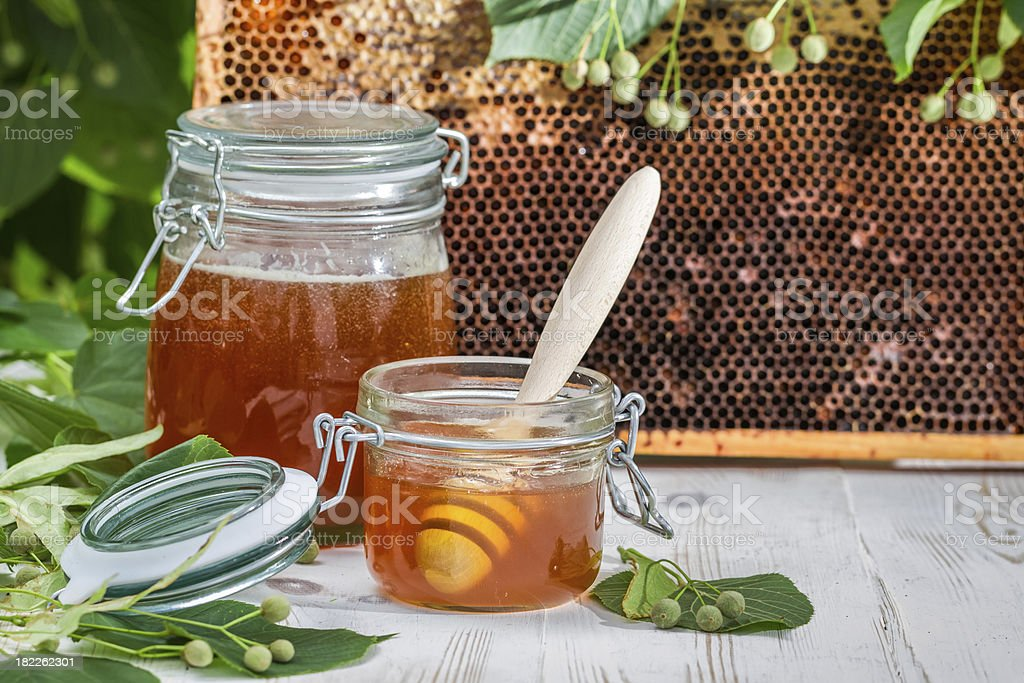 Honey in a jar and honeycomb with linden tree royalty-free stock photo
