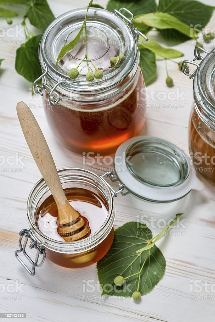 Honey in a jar and lime leaves royalty-free stock photo