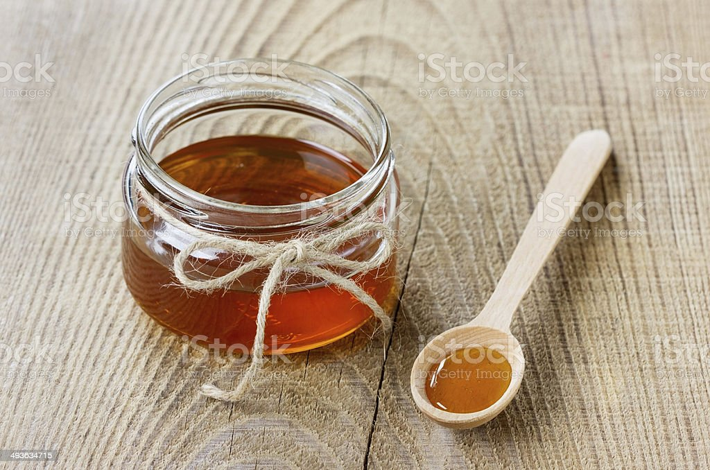 Honey in a spoon and jar on a rustic background stock photo