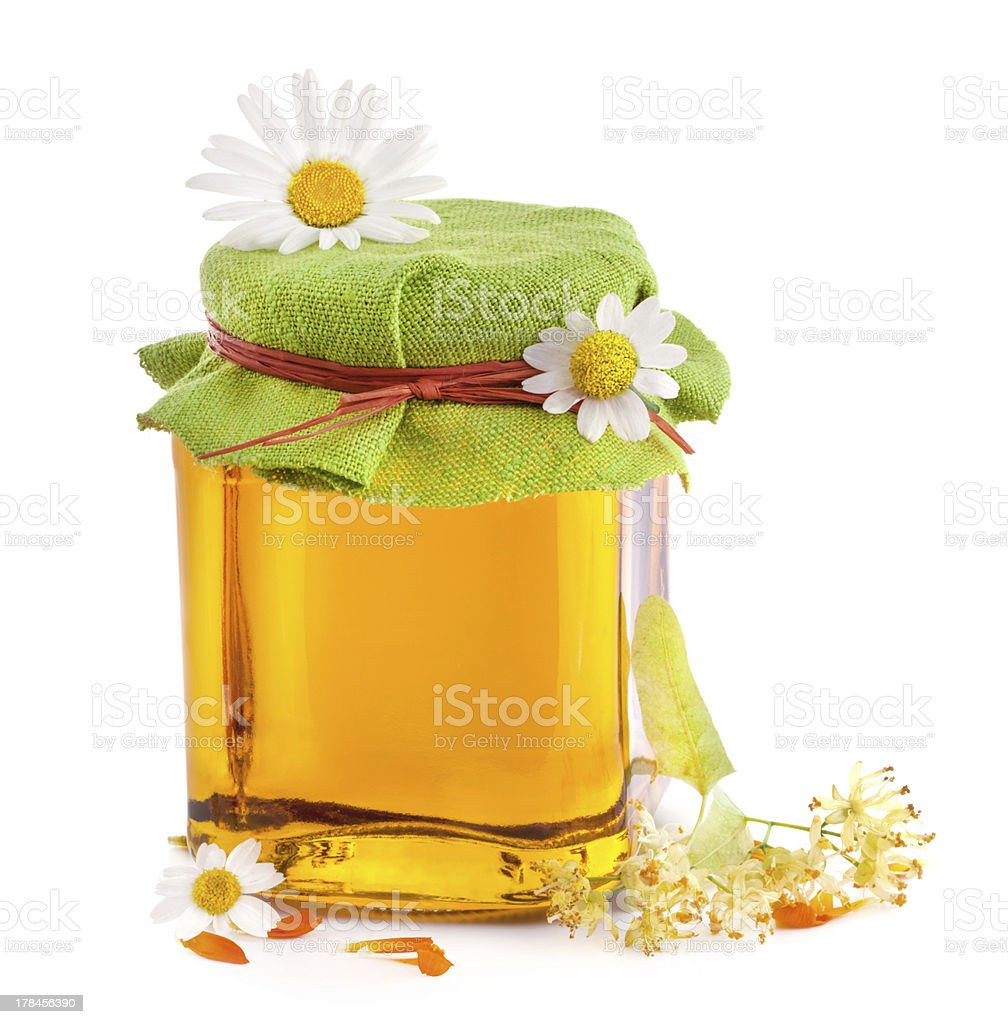 Honey in glass jar with flowers royalty-free stock photo
