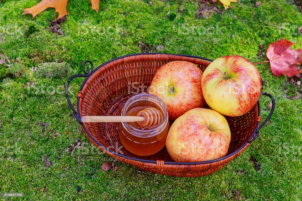 Honey in glass with flowers melliferous herbs autumn apples stock photo