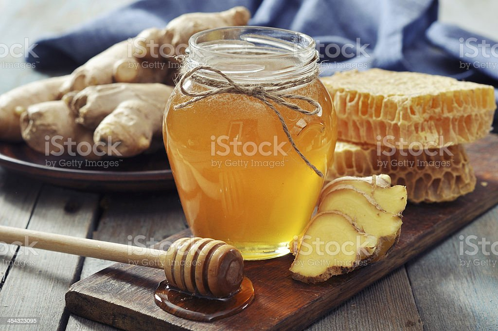 Honey in jar with fresh ginger stock photo