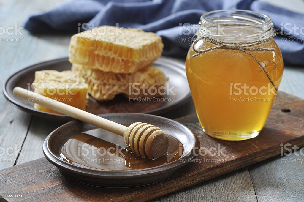Honey in jar with honeycombs stock photo