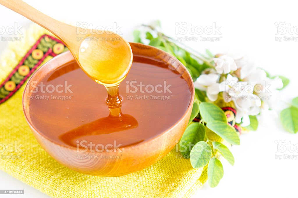 Honey in wooden bowl stock photo