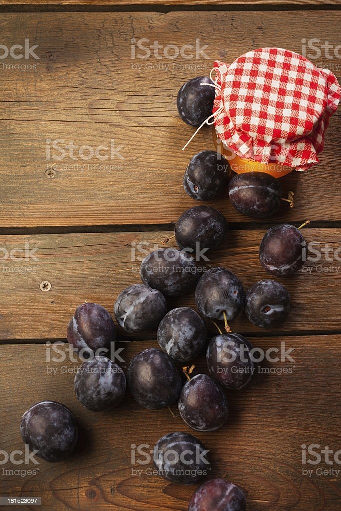 Honey jar and plums on picnic table. royalty-free stock photo