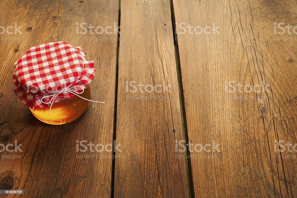 Honey jar on picnic table royalty-free stock photo