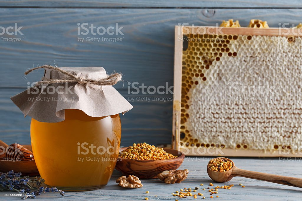 Honey jar with honeycombs and pollen stock photo