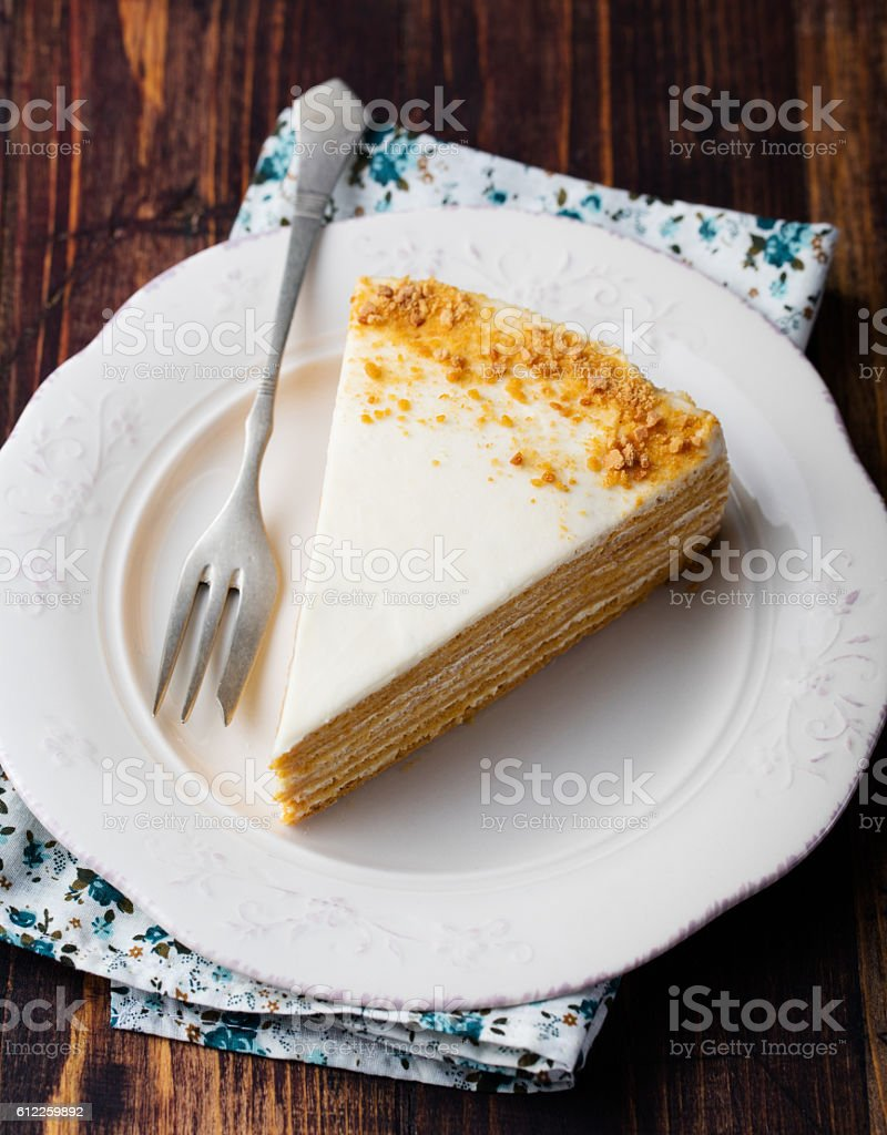 Honey layered cake on a white plate, wooden background stock photo