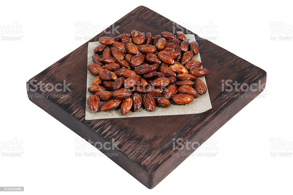 Honey roasted almonds on red brown serving board on white. stock photo