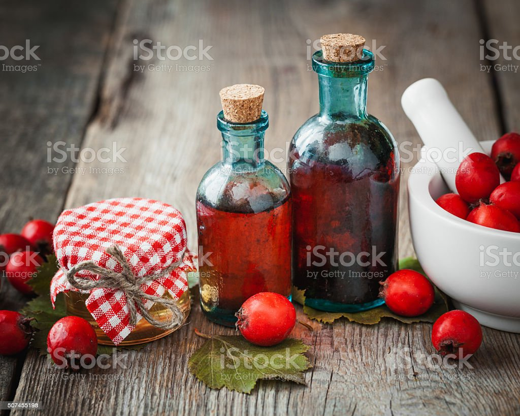 Honey, tincture bottles and mortar of hawthorn berries stock photo