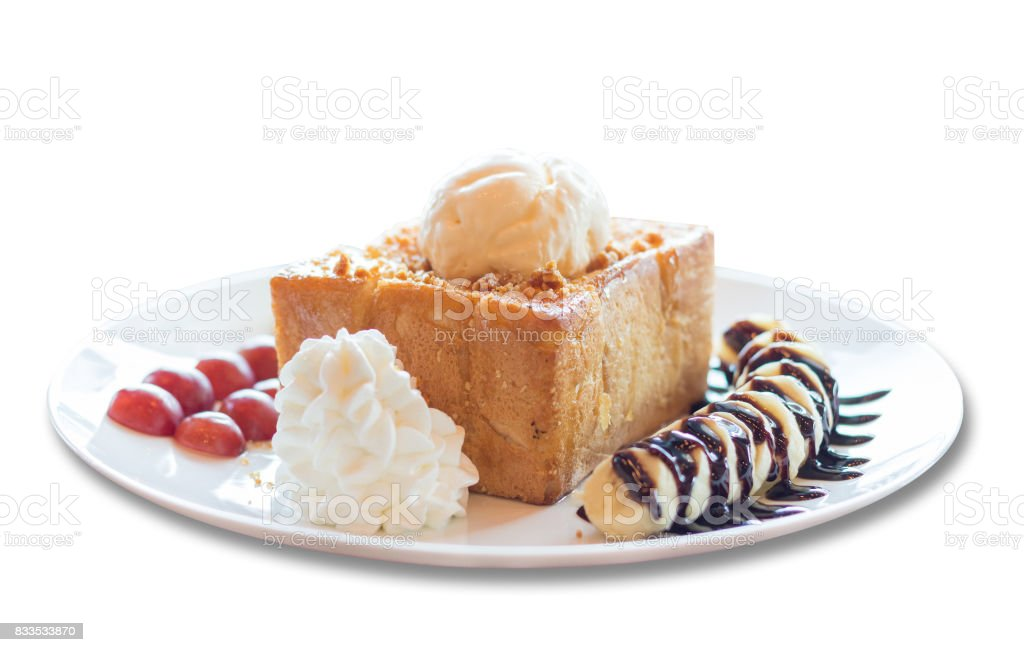 Honey toast with vanilla ice cream, whipped cream and chocolate syrup. Served with banana, grape and apple stock photo