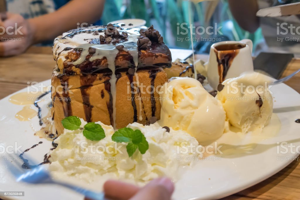 honey toast with vanilla ice-cream and chocolate on plate stock photo