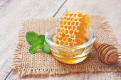 honeycomb in glass bowl with a wooden honey dipper