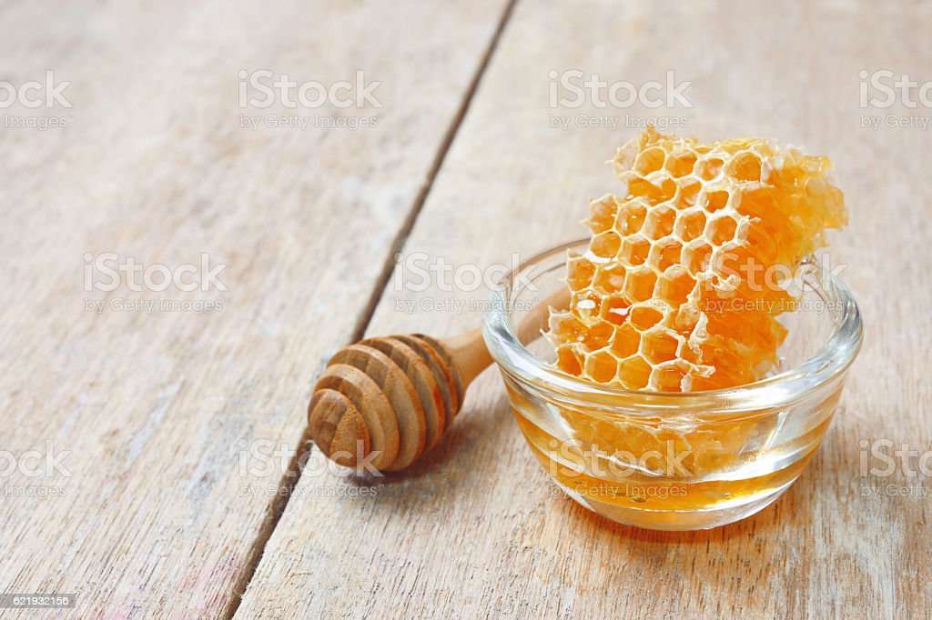 honeycomb in glass bowl with a wooden honey dipper stock photo