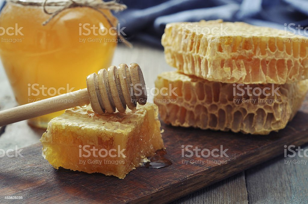 Honeycomb with honey dipper stock photo