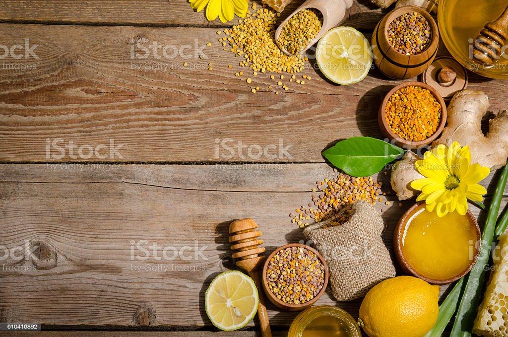 honeycombs ,honey, ginger, pollen, lemon on a wooden table stock photo