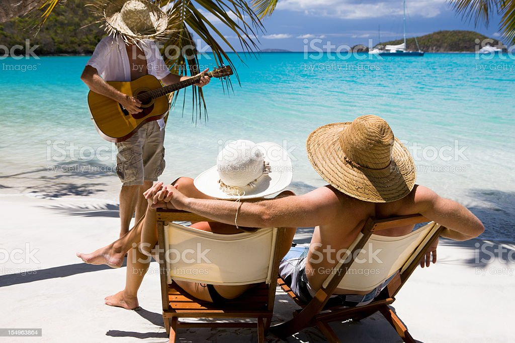 honeymoon couple at the beach listening a musician playing guitar stock photo
