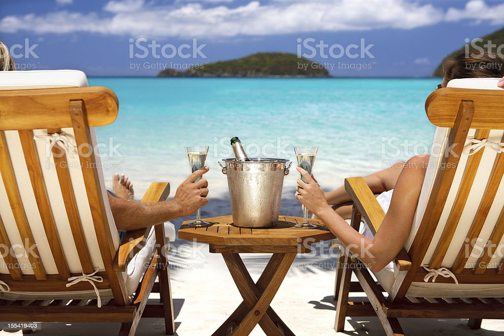 honeymoon couple in recliners drinking champagne at a Caribbean beach stock photo