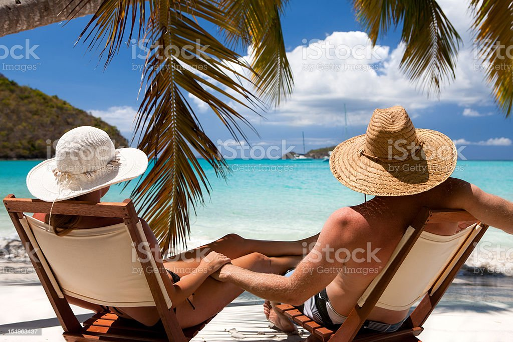 honeymoon couple relaxing at a Caribbean beach on summer vacation stock photo