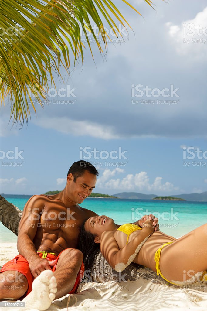 honeymoon couple relaxing under palm tree at the Caribbean beach royalty-free stock photo