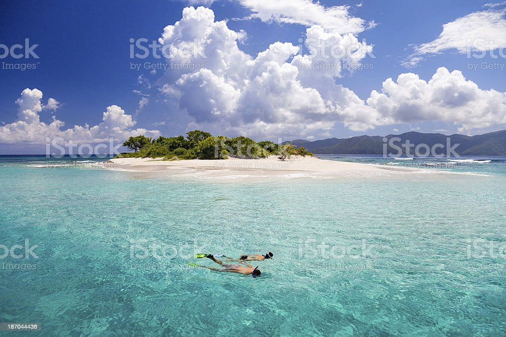 honeymoon couple snorkeling by tropical island in the Caribbean stock photo