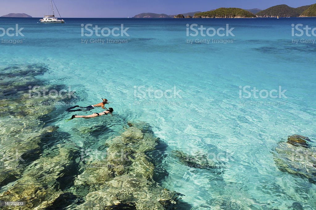 honeymoon couple snorkeling in the Caribbean waters stock photo
