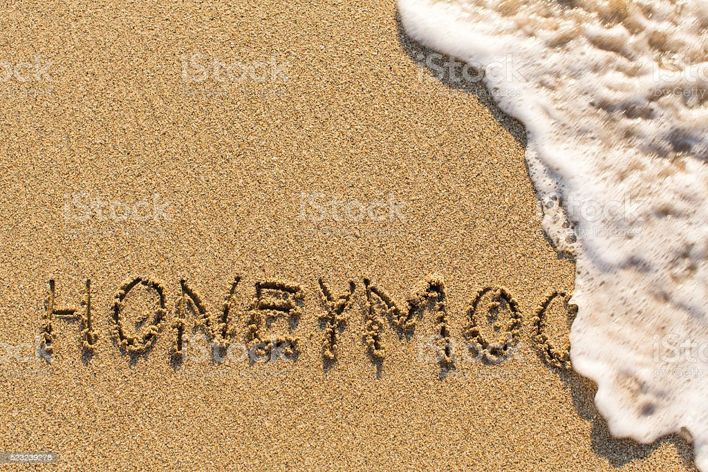 Honeymoon - drawn of the hand on the beach sand stock photo