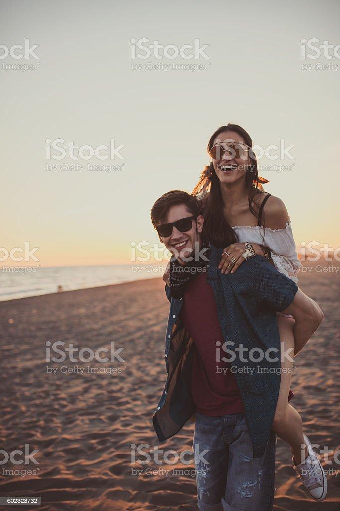 Honeymoon piggyback ride on the beach stock photo