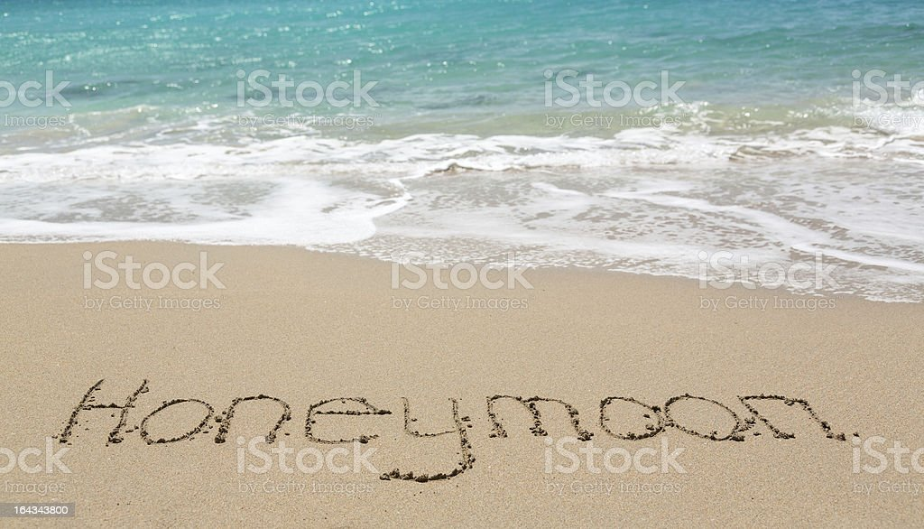 Honeymoon written in sand with sea surf royalty-free stock photo