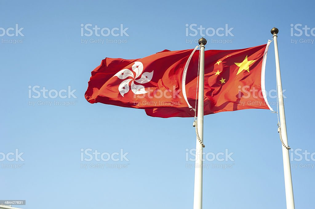 Hong Kong and China flags flying against a blue sky stock photo