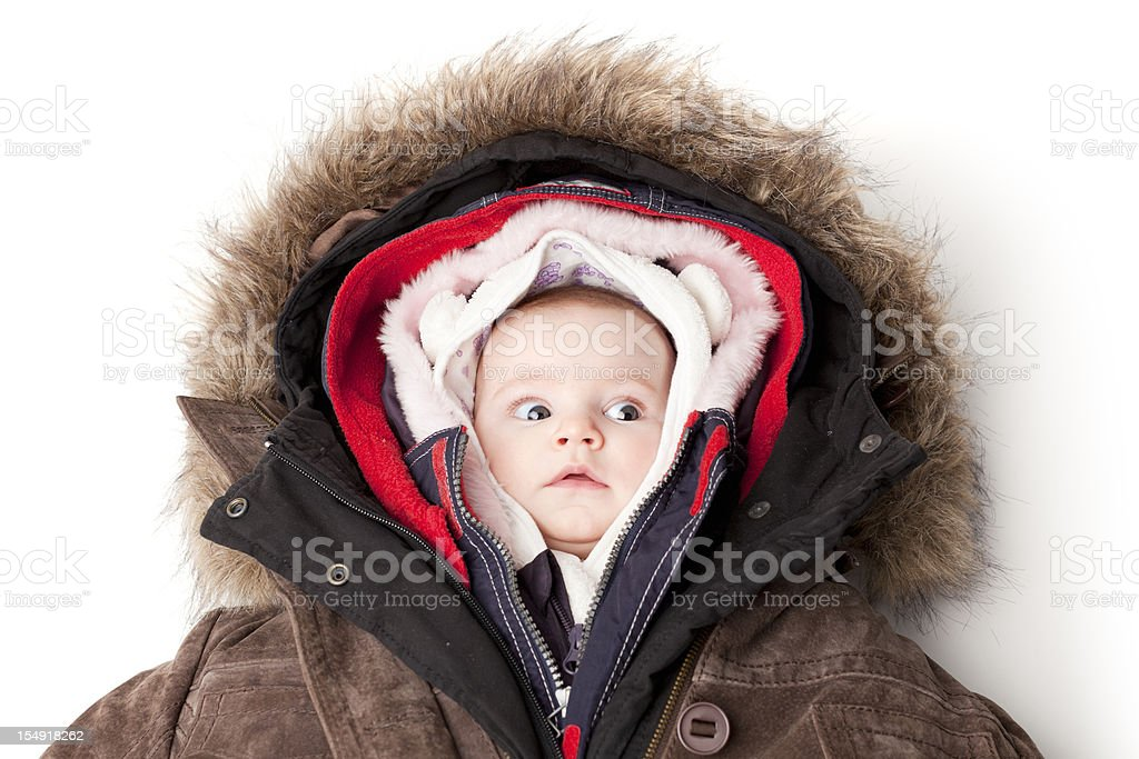 Hooded baby. Little girl in many winter jackets. stock photo