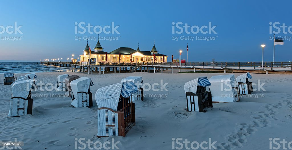Hooded beach chairs and illuminated pier on sand coast stock photo