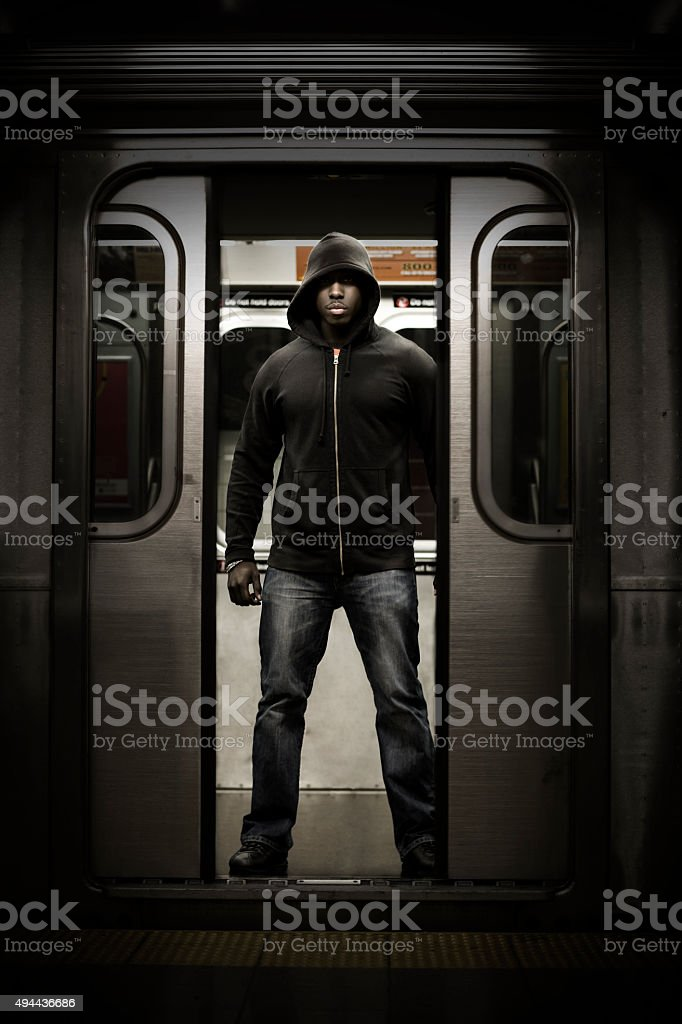 Hooded Black Man In Doorway Of Subway stock photo