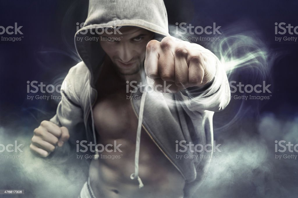 Hooded boxer punching an enemy stock photo
