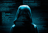hooded computer hacker in the shadow with program codes