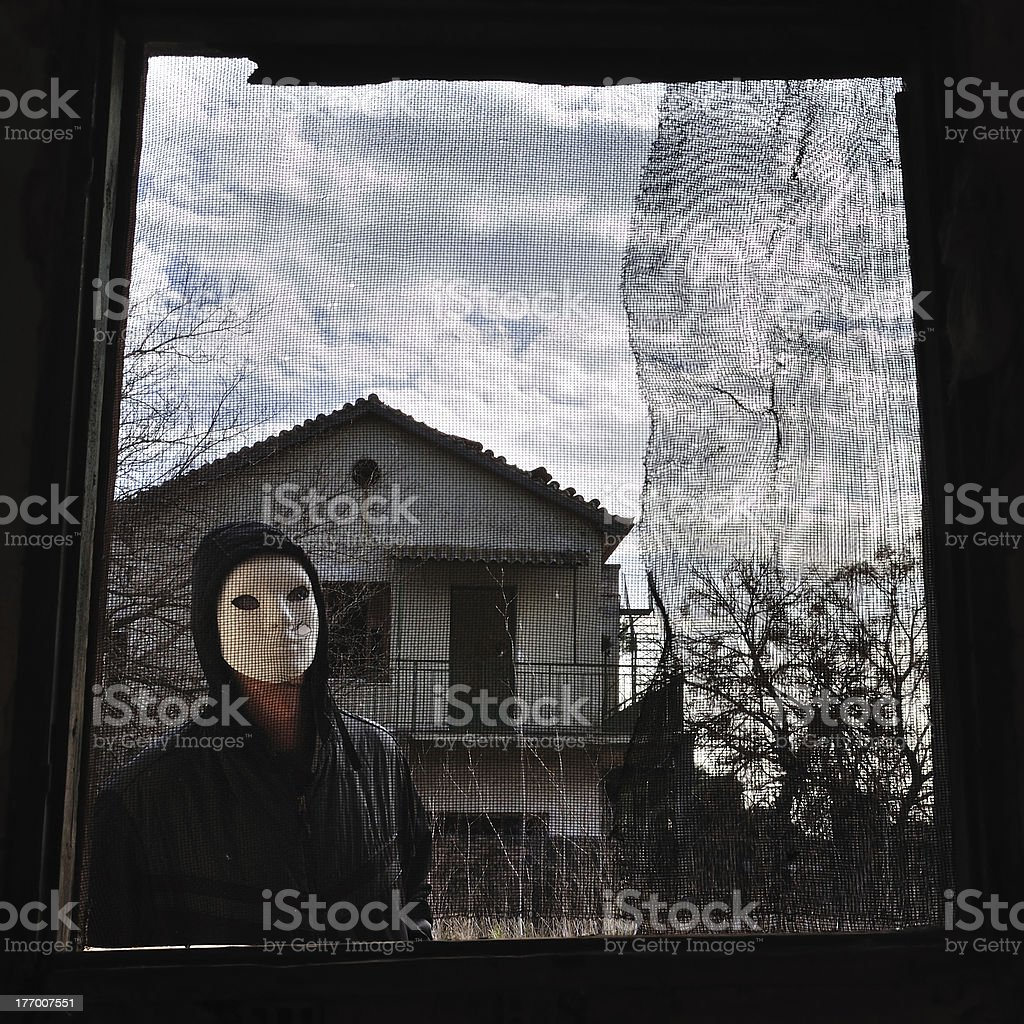 hooded figure threaded window royalty-free stock photo