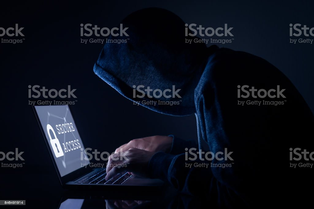 Hooded hacker doing cyber attack to secure access, computer screen stock photo