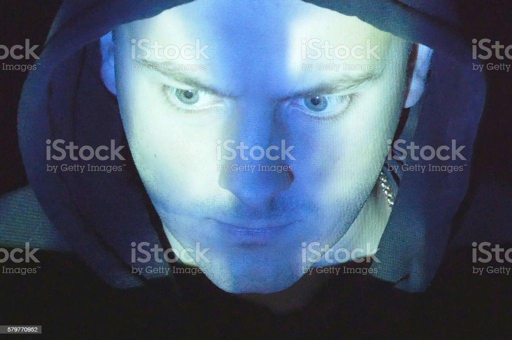 Hooded hacker working on a computer, foto de stock libre de derechos