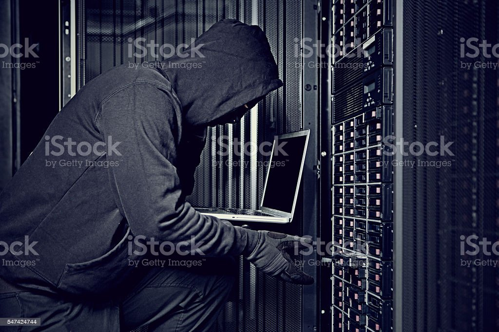 Hooded male hacker using laptop in server room stock photo