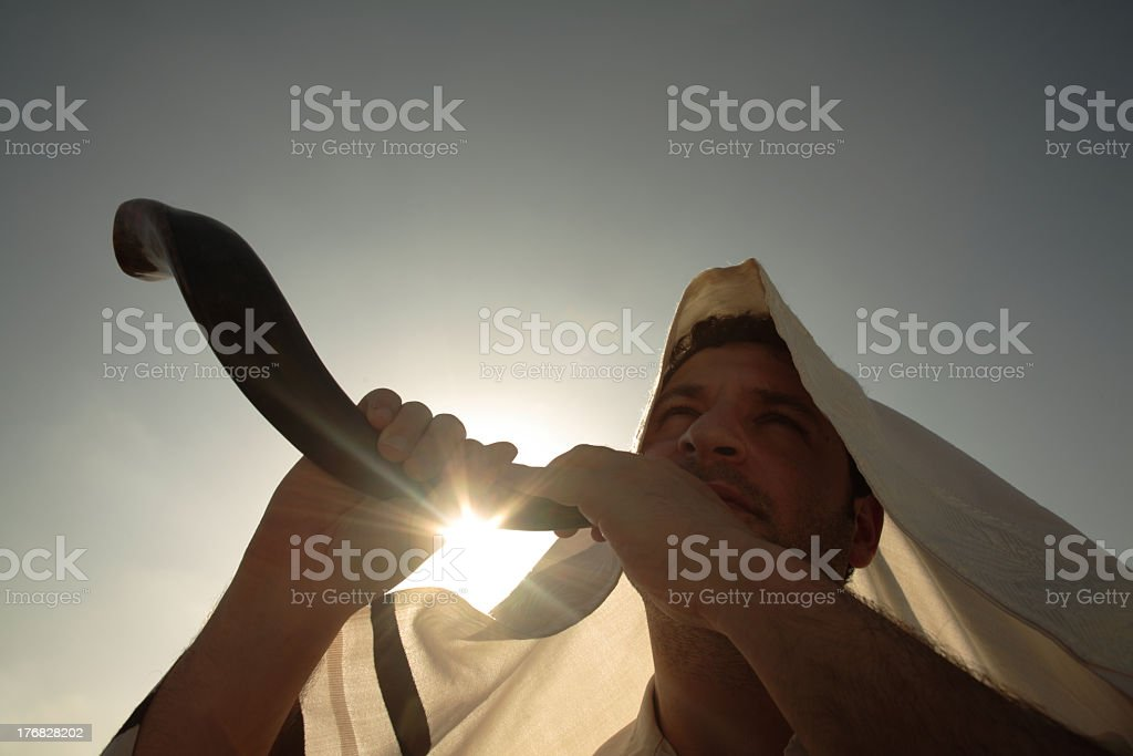 Hooded Man sounding a shofar on a sunny day stock photo
