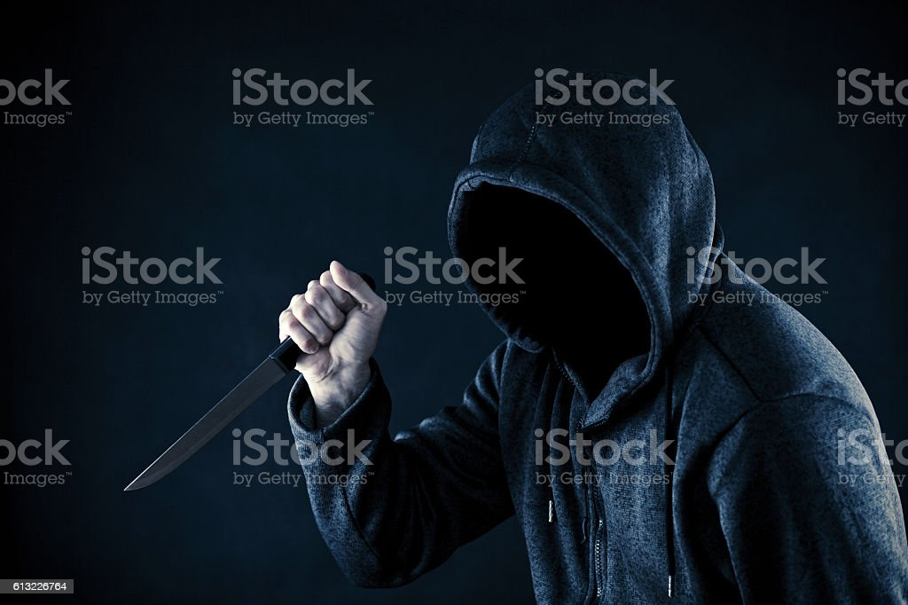 Hooded man with knife in the dark stock photo