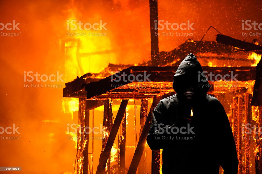 Hooded person holding a lighter in front of burning house stock photo