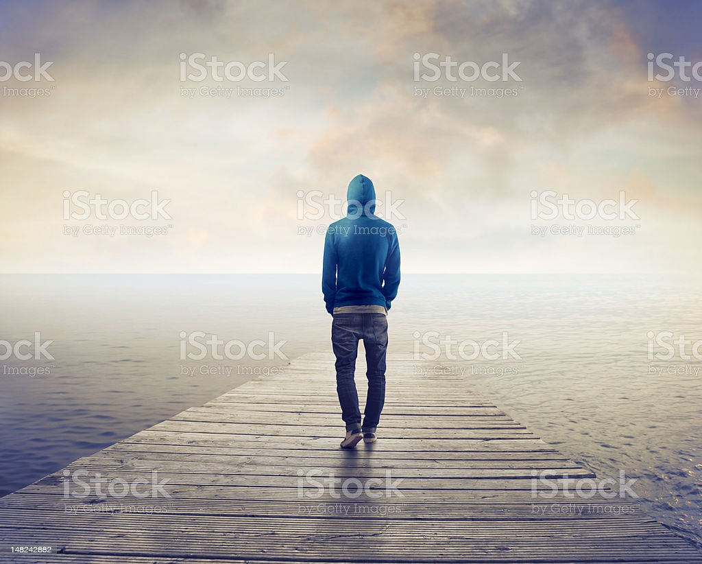 Hooded person walking on wooden pier towards the sea royalty-free stock photo