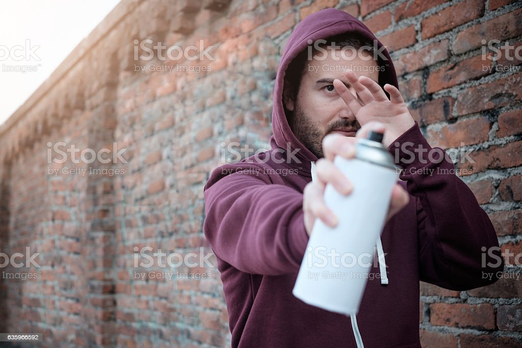 Hooded tagger hiding himself stock photo
