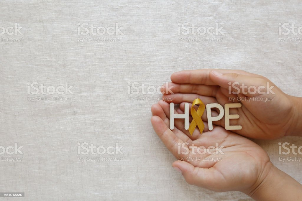 Hope with yellow gold ribbons on hands, Sarcoma Awareness, Bone cancer, Liver cancer, Bladder Cancer, childhood cancer awareness stock photo
